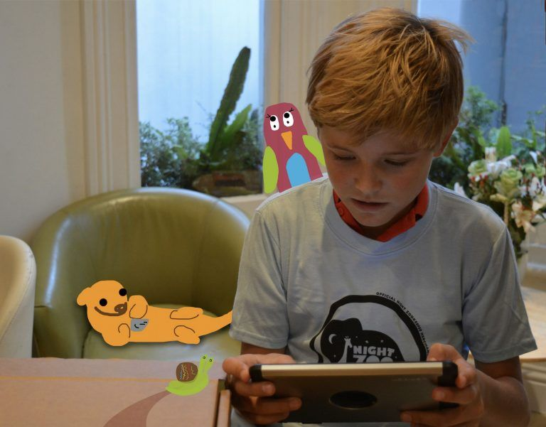 Child on iPad with Night Zookeeper characters.