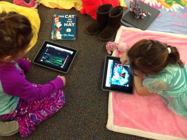 Children on blankets with ipads.
