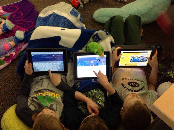 Three children on iPads.